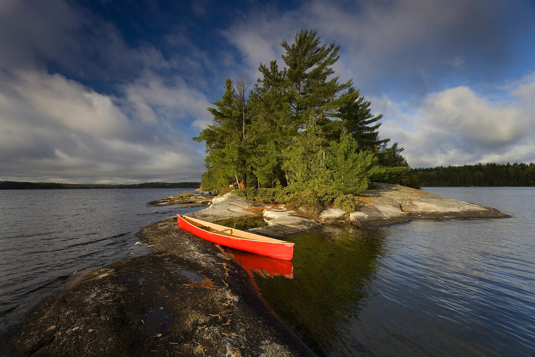 Red canoe beside a small rock island on peaceful lake.