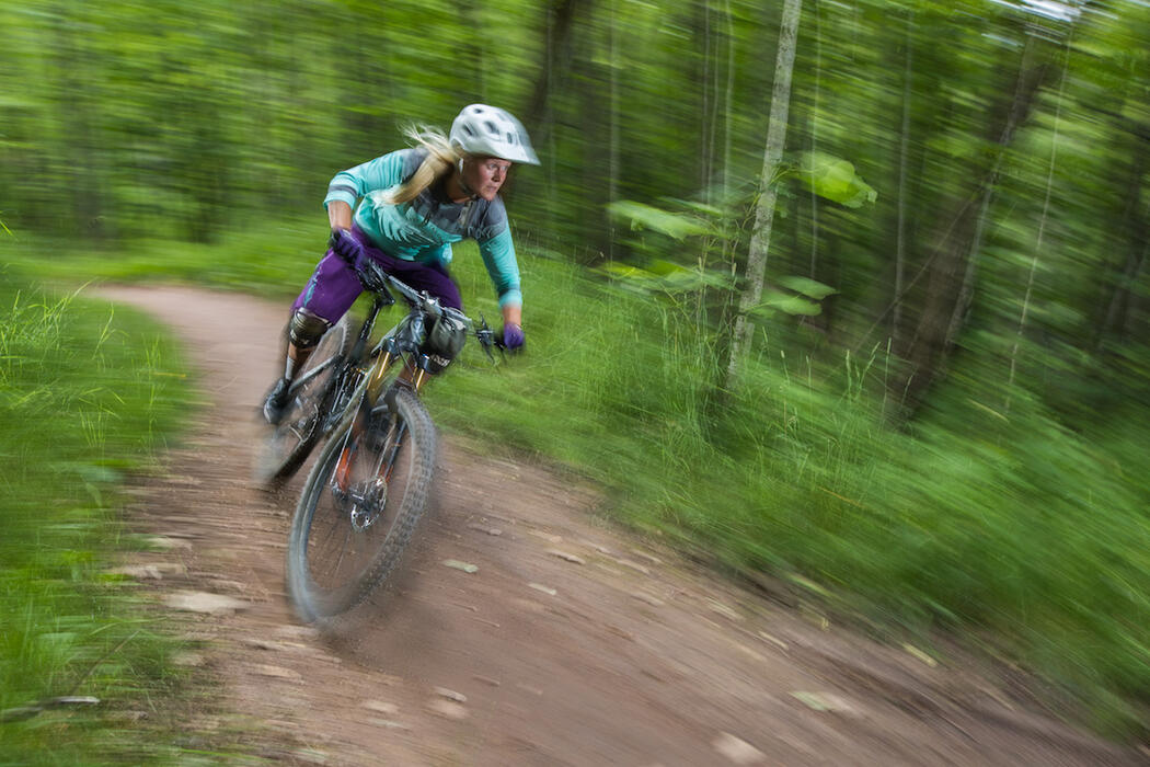 Woman in action mountain biking in forest