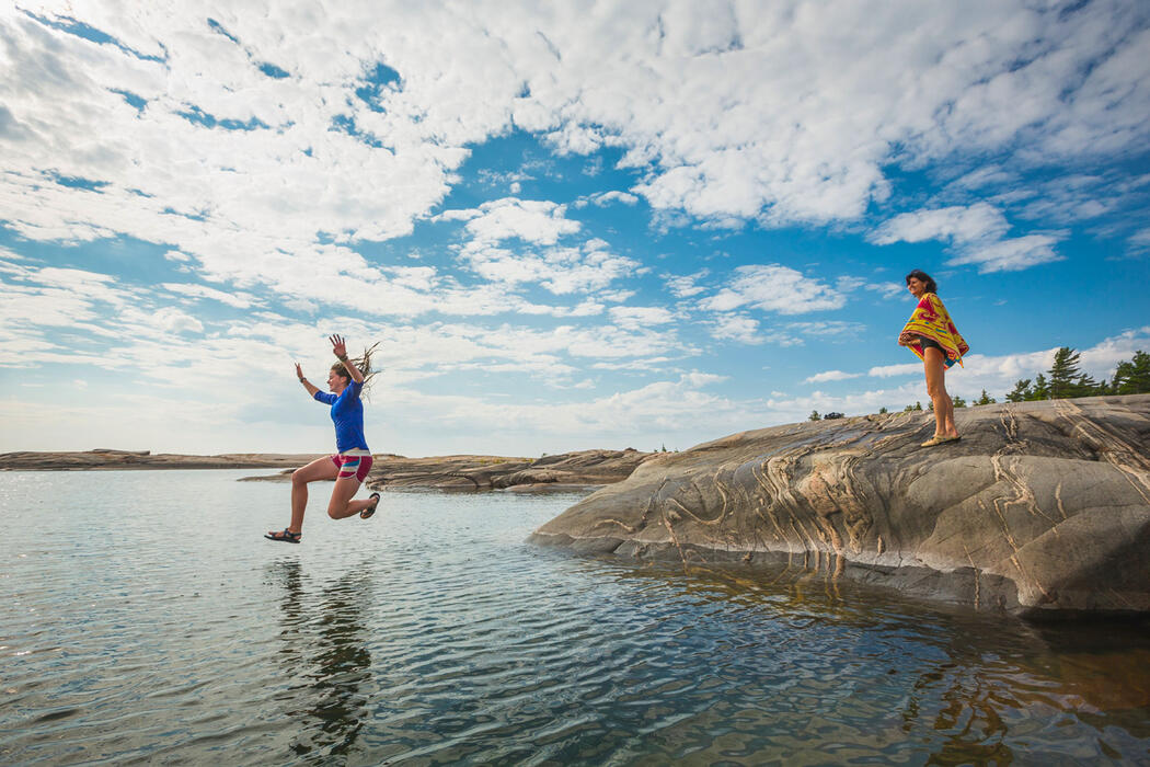 Woman jumping into the water from a rock with other woman watching
