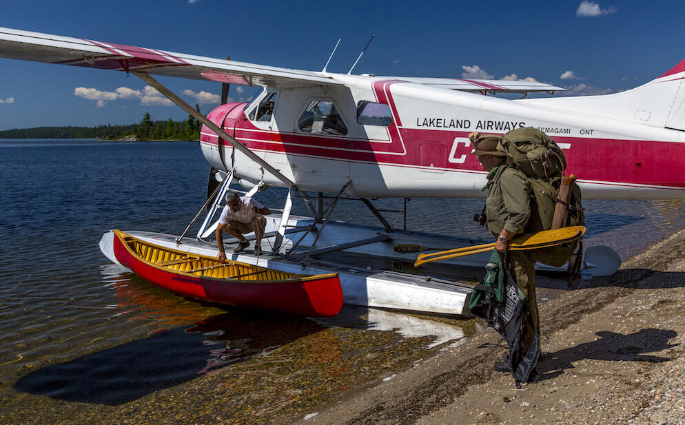 Man with pack and paddles standing near floatplane with canoe.