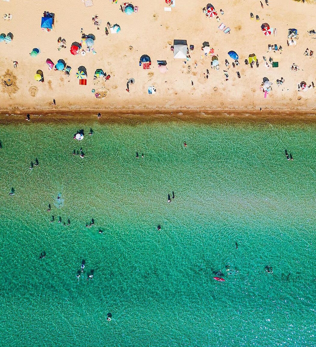 Aerial view of sandy beach and turquoise waters with lots of people.