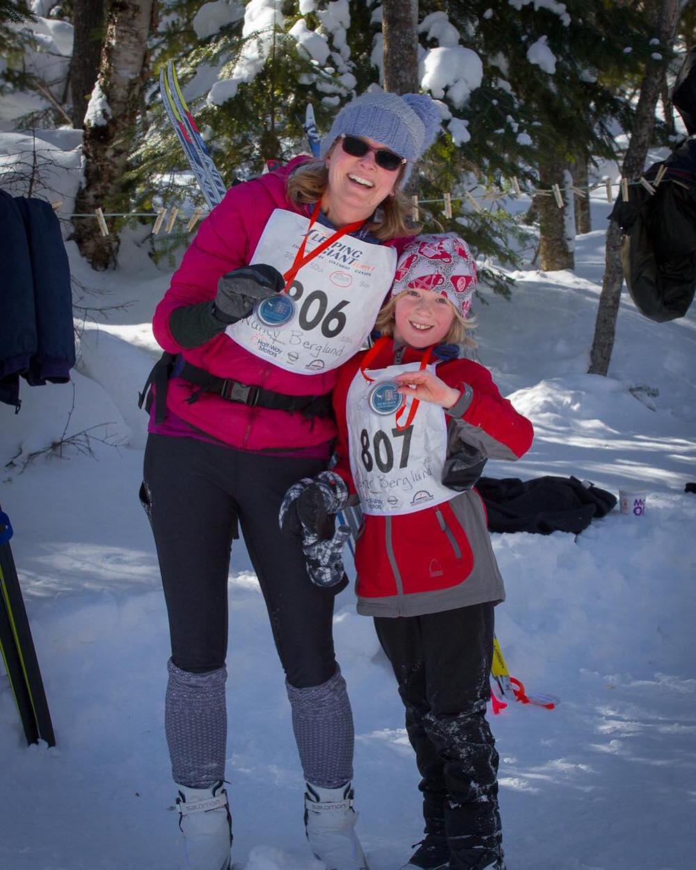 Woman and child showing metals from x-c ski race