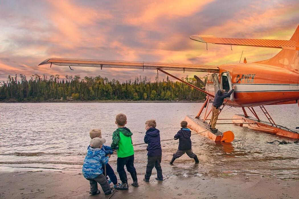 Group of kids on a beach holding a rope tied to a floatplane.