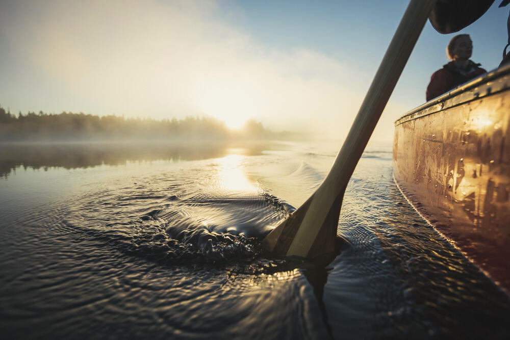 Side of a canoe and paddle in water at sunrise