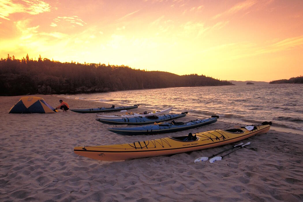 Group of kayaks pulled up on a sandy beach with tent at sunset