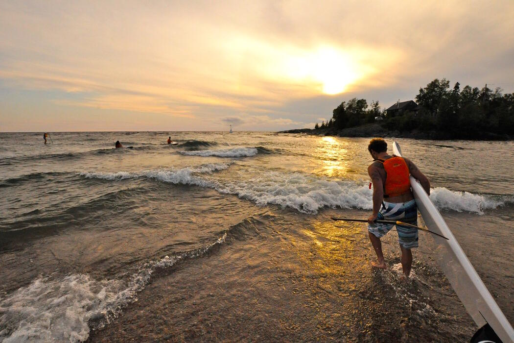 Man with SUP board going into Lake Superior at sunset.