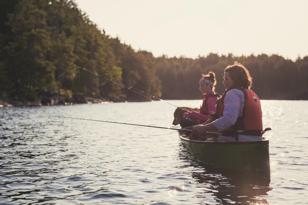 Man and woman fishing from a green canoe.