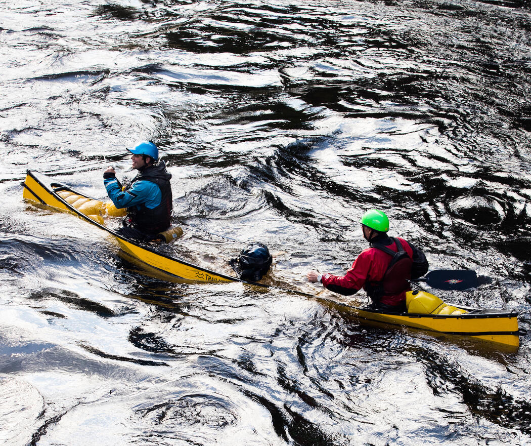 Two paddlers in water-filled canoe
