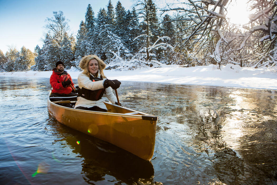Woman and man in winter clothing paddling a yellow canoe along snow-covered shoreline