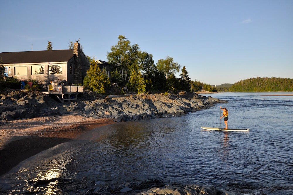 Woman paddling a SUP board in front of Rock Island Lodge.