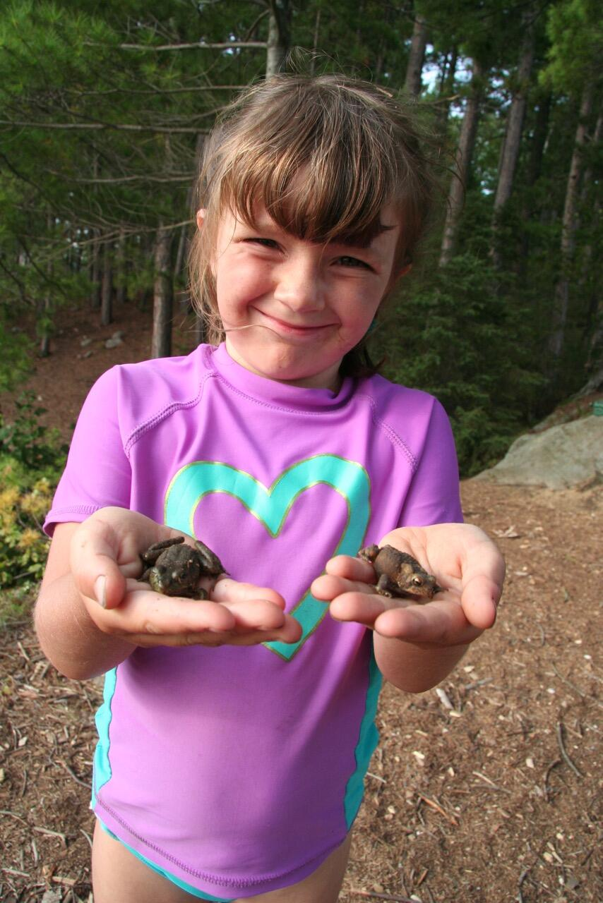 Young girl holding two frogs