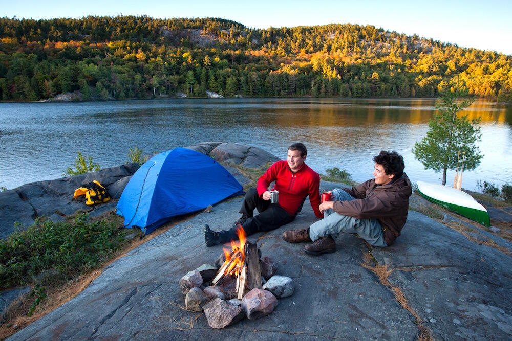 Two men sitting by a campfire overlooking lake - tent and canoe in background.
