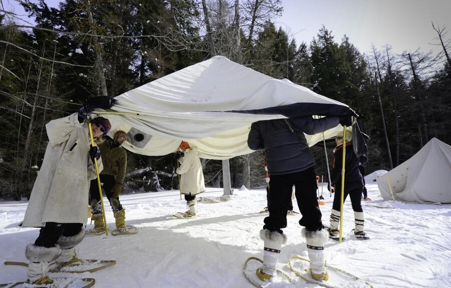 Group of people putting up large white canvas tent