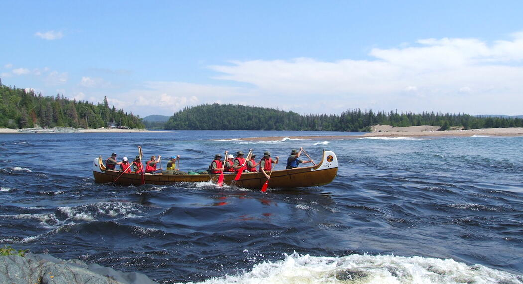 People paddling a voyageur canoe on Lake Superior.