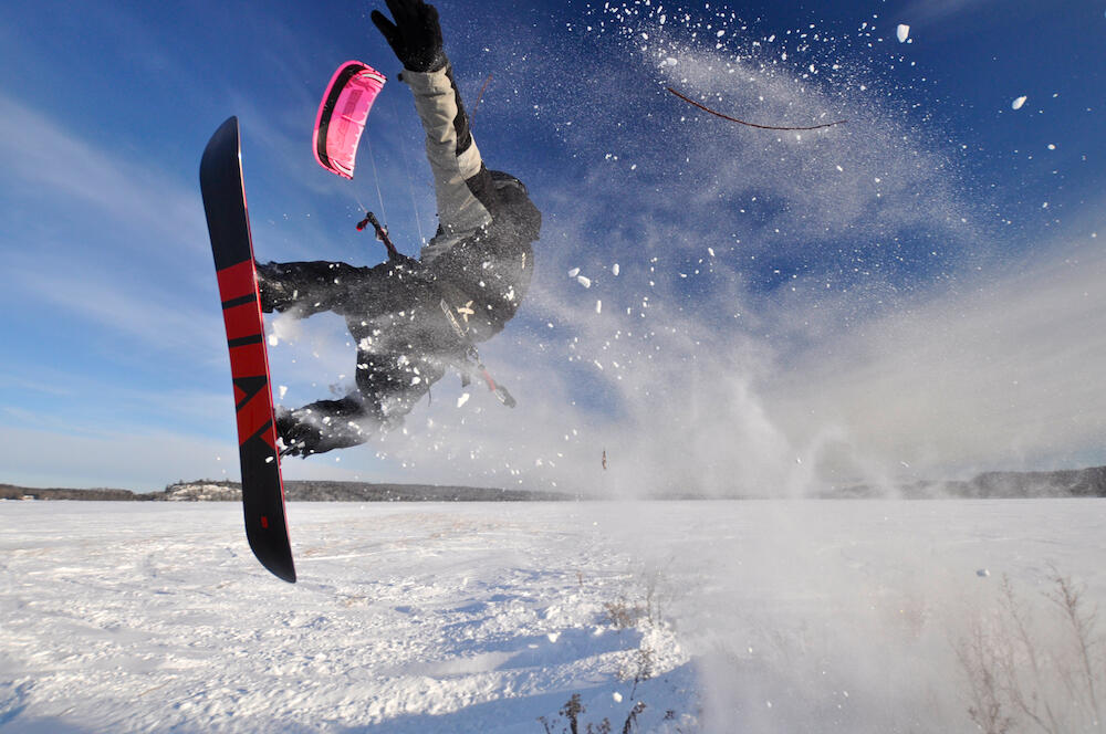 Person catching some air on a snowboard on a frozen lake