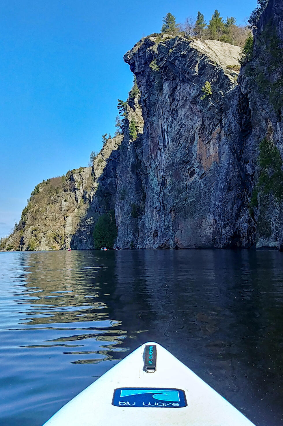 Front end of SUP board on lake looking up a towering cliffs
