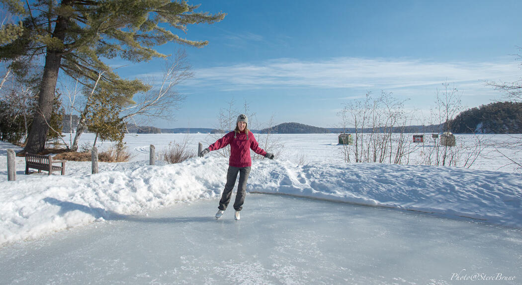 Woman skating on outdoor rink beside a lake.