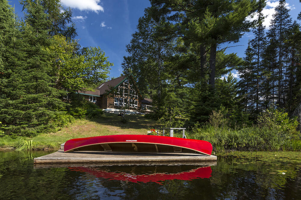 Canoe resting on a dock in front of a lodge.