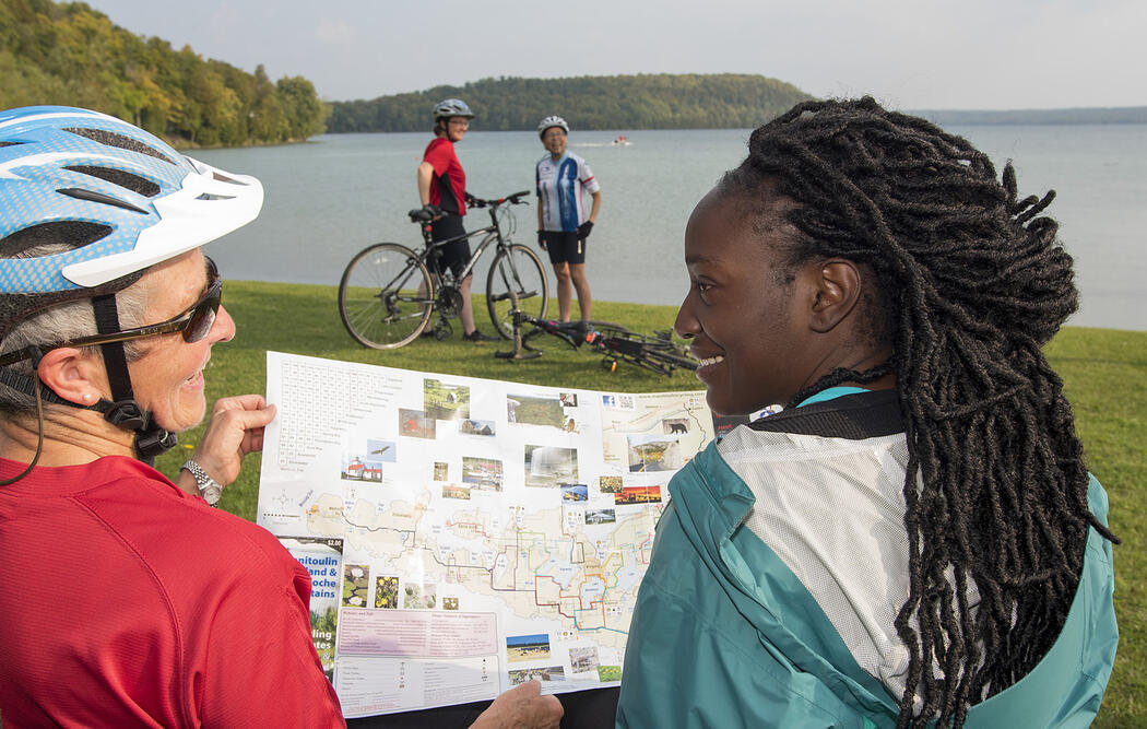 Two cyclists holding a map with two people standing by bicycles.