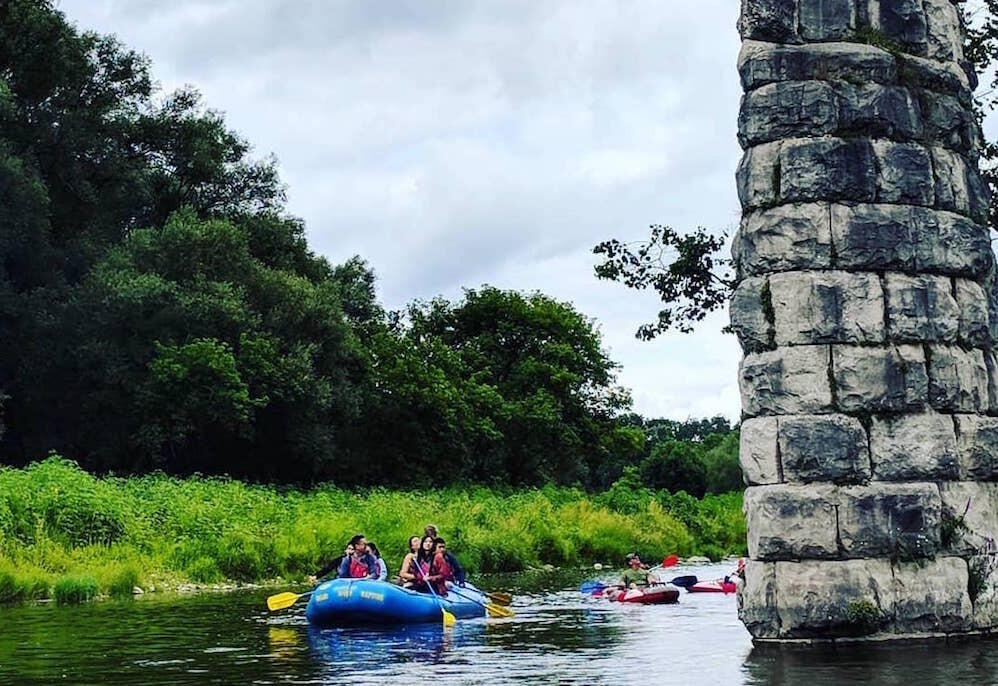 Six person raft floating by a stone pillar on the Grand River.