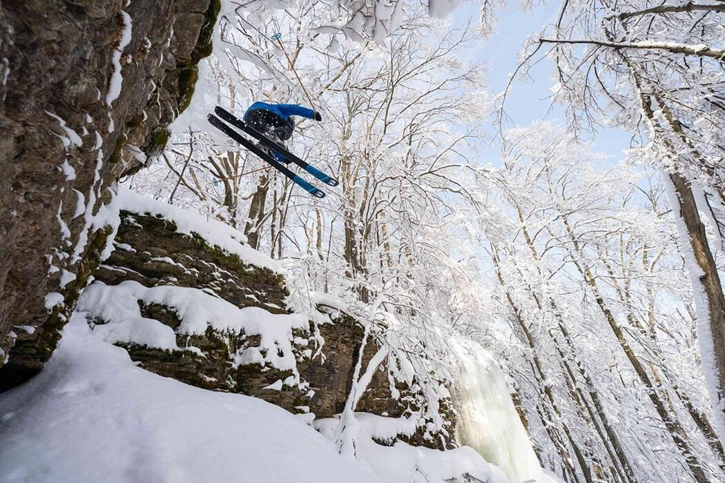 Man jumping with skiis off a rock cliff in winter.