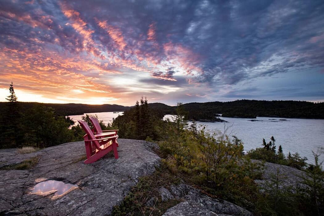 Two red Muskoka chairs perched on top of a top overlooking sunset on Lake Superior.