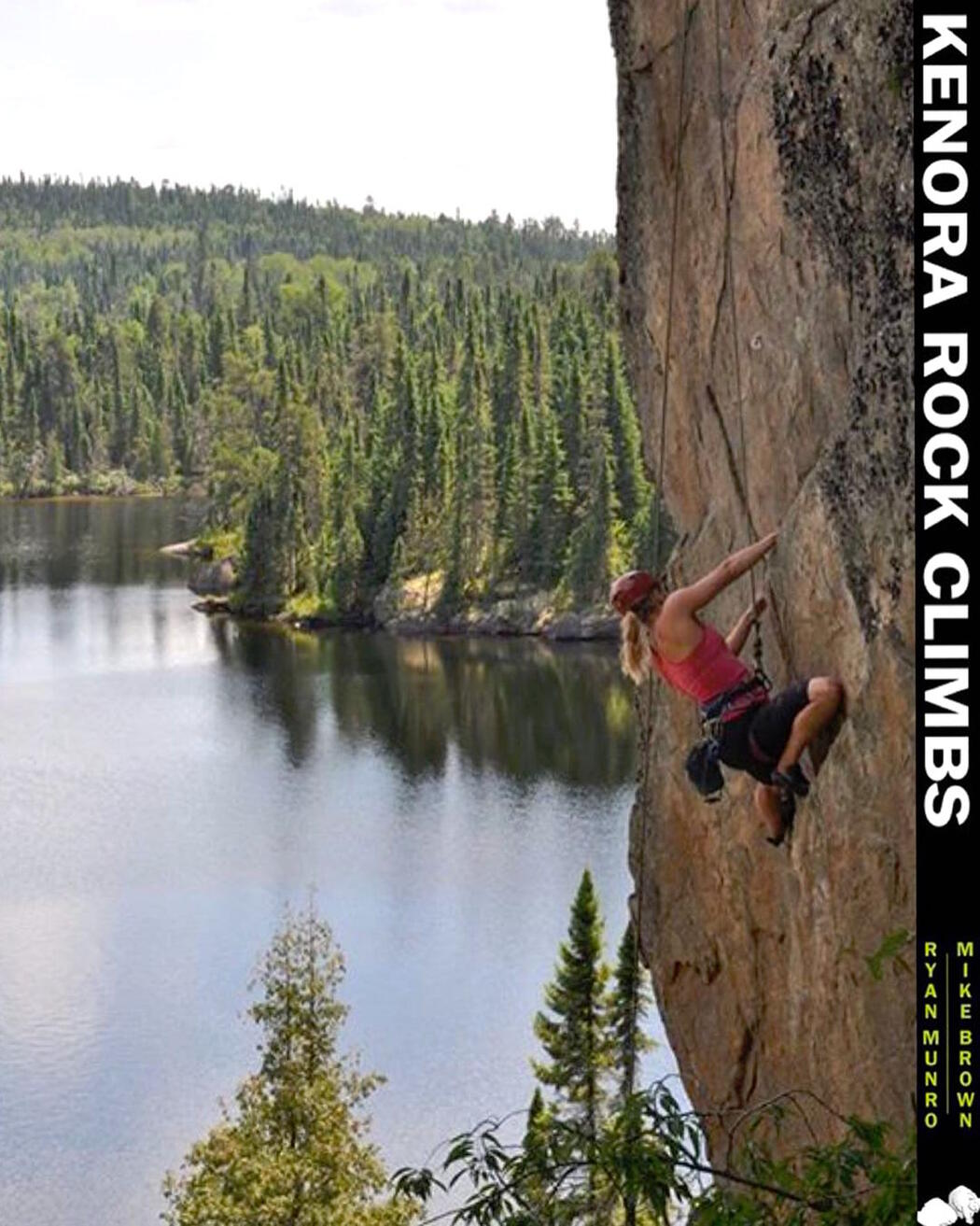 Woman climbing a vertical rock face with lake in background.