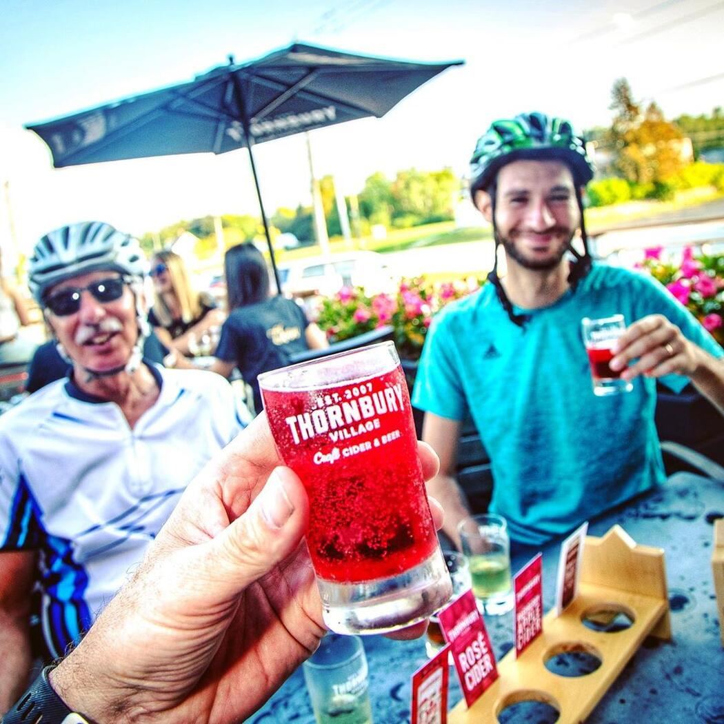 Cyclists enjoying apple cider drinks at a outdoor table.