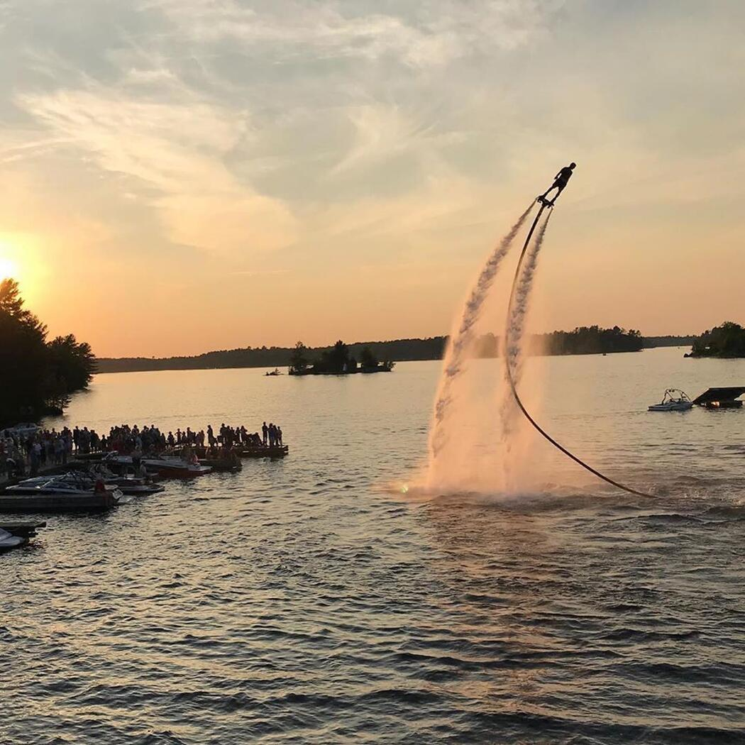 A stunt flyboarder high in the air over a lake.