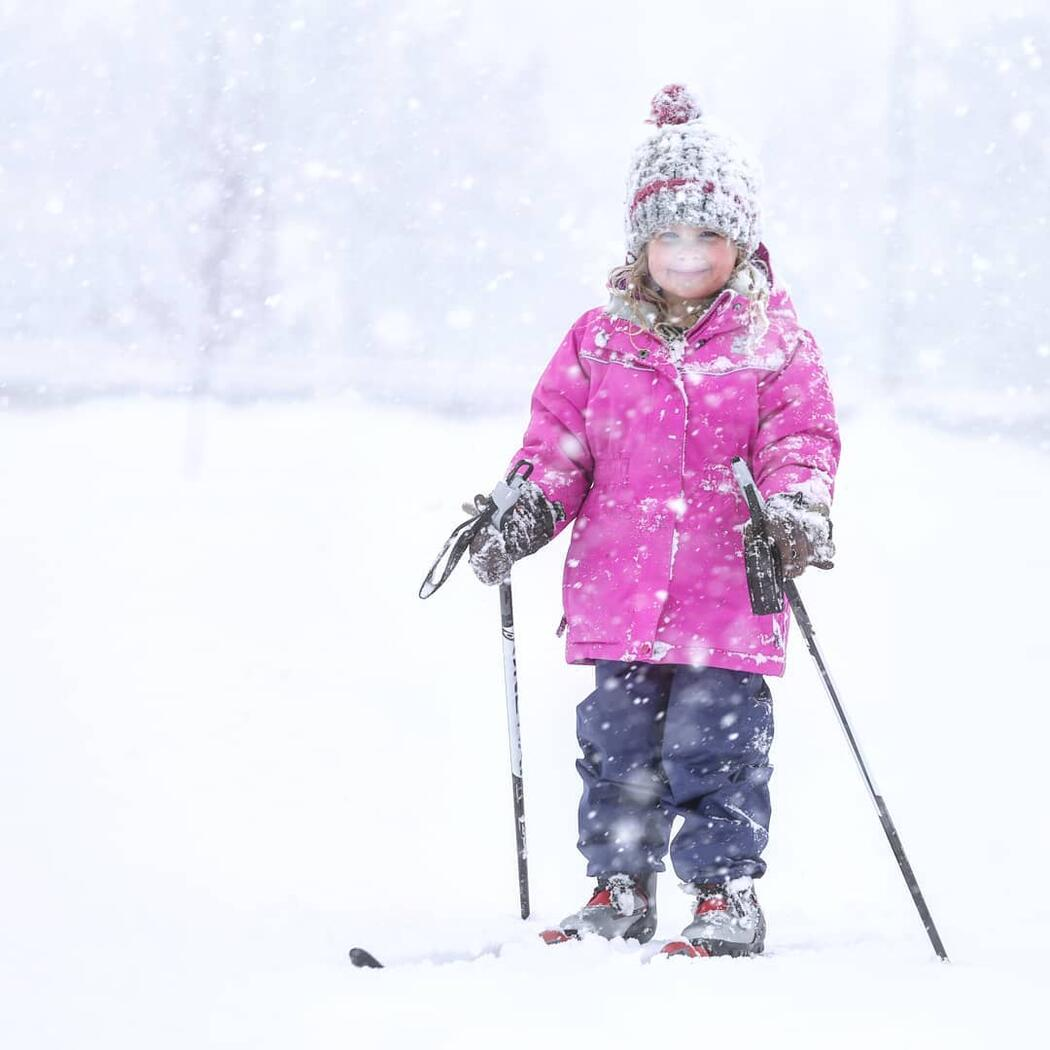 Young girl in pink jacket cross country skiing.in snow storm.