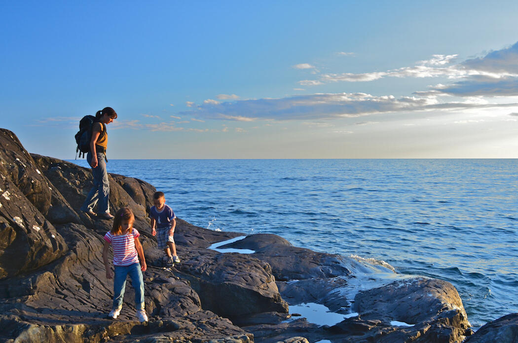 Woman and two children play on rocky shoreline