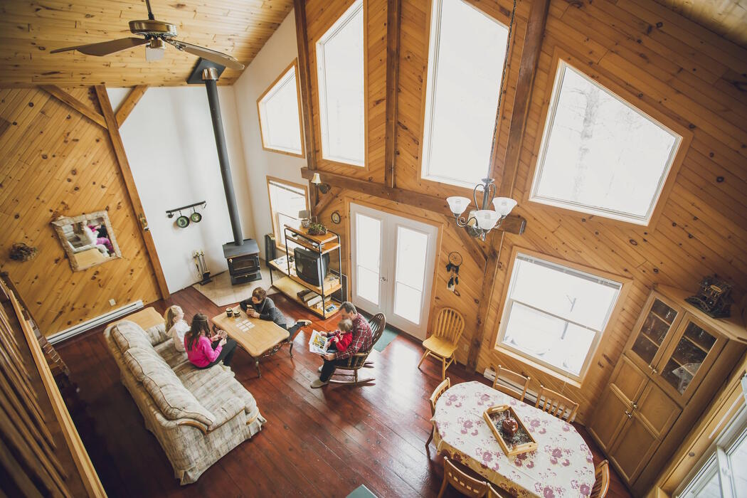 Family sitting on couches in cozy cabin.