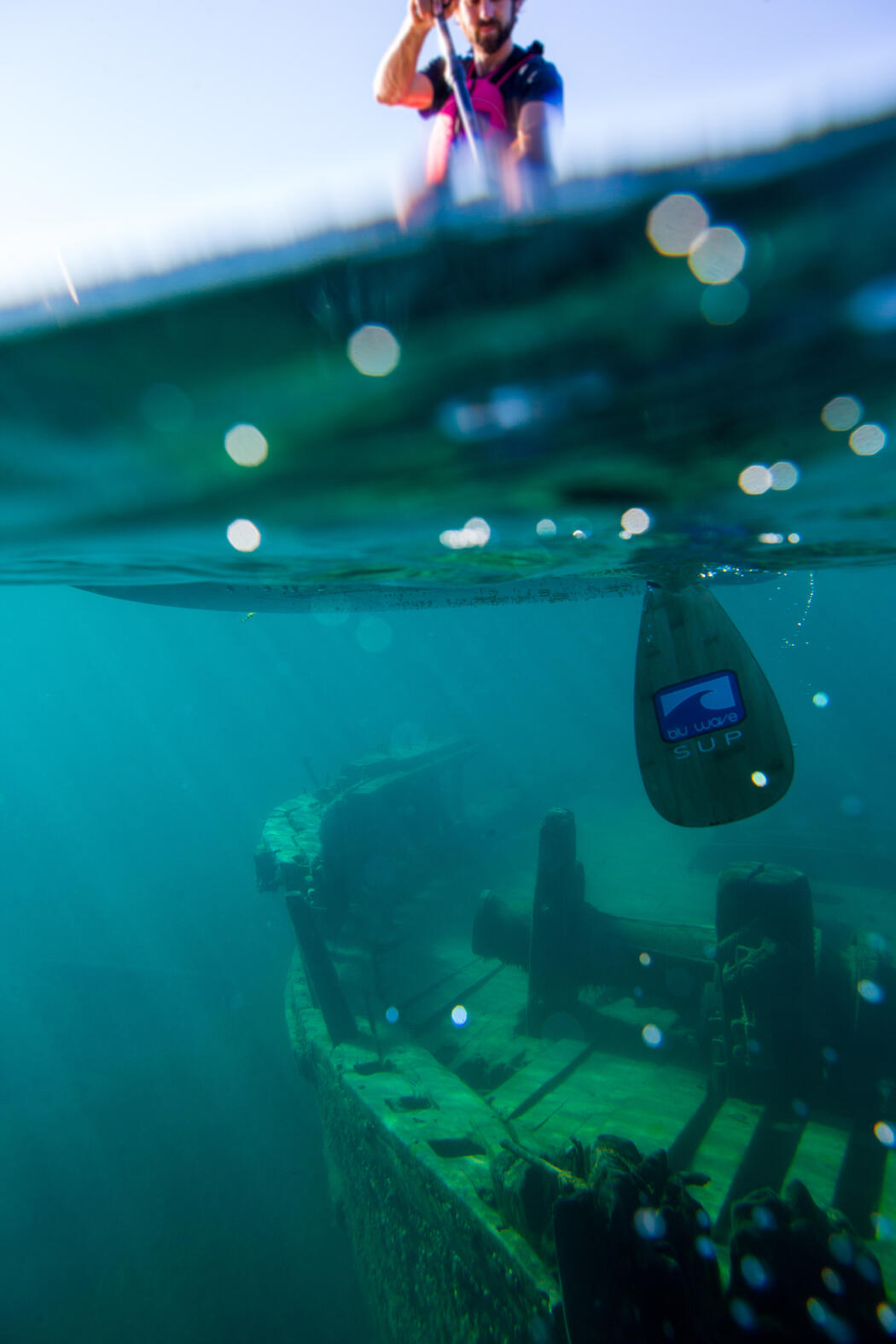 Underwater image of shipwreck with a kayaker looking down from above