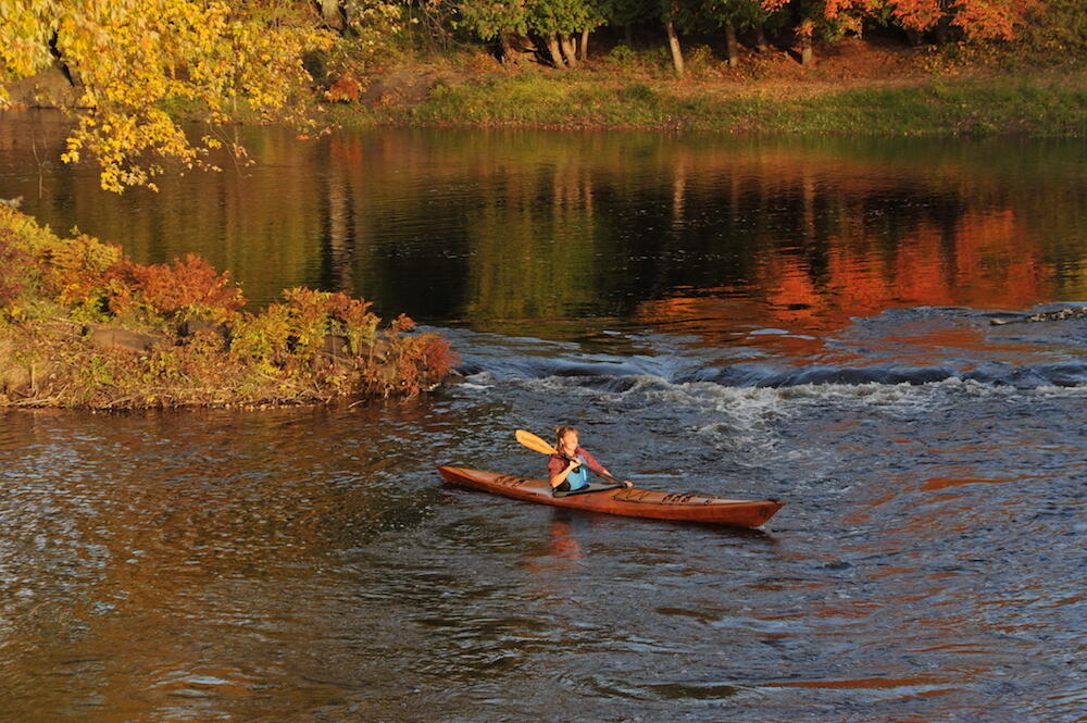 Woman kayaking on a calm river in fall.