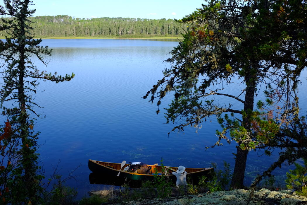 Woman on shore beside a canoe and serene lake.