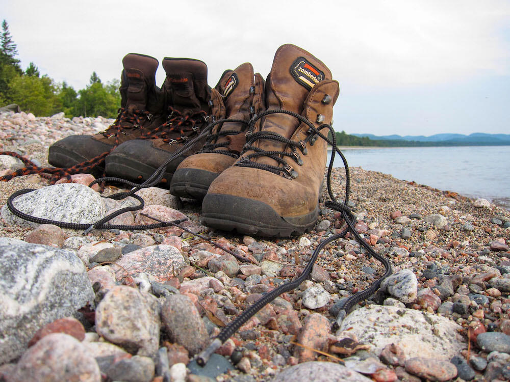 Two pairs of leather hiking boots on rocky beach