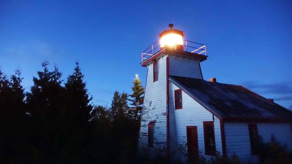 Old wooden lighthouse with light on at night.