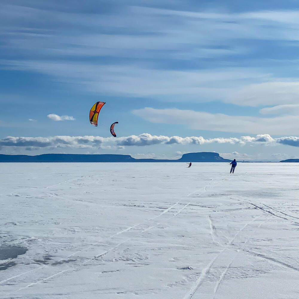 Several snowkiters gliding on a large lake.