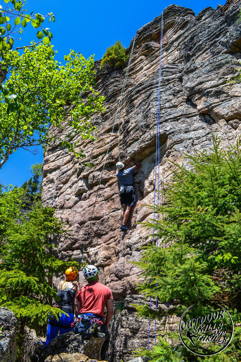 Ropes hanging from top of rock face with a climber ascending.