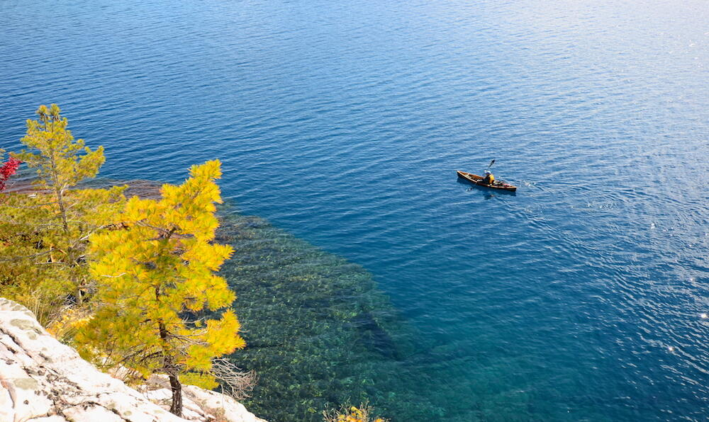 View of a canoe on a turquoise lake from high on a hill