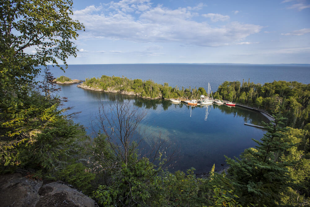 View of beautiful sheltered bay with sailboats from top of a cliff
