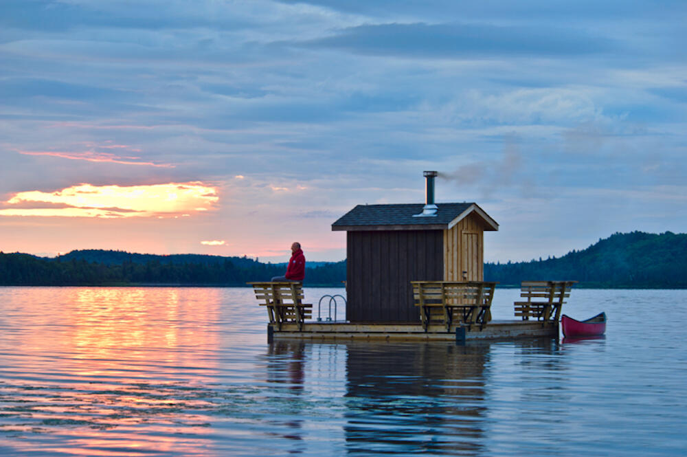 Sauna with deck and canoe floating on a lake at sunset