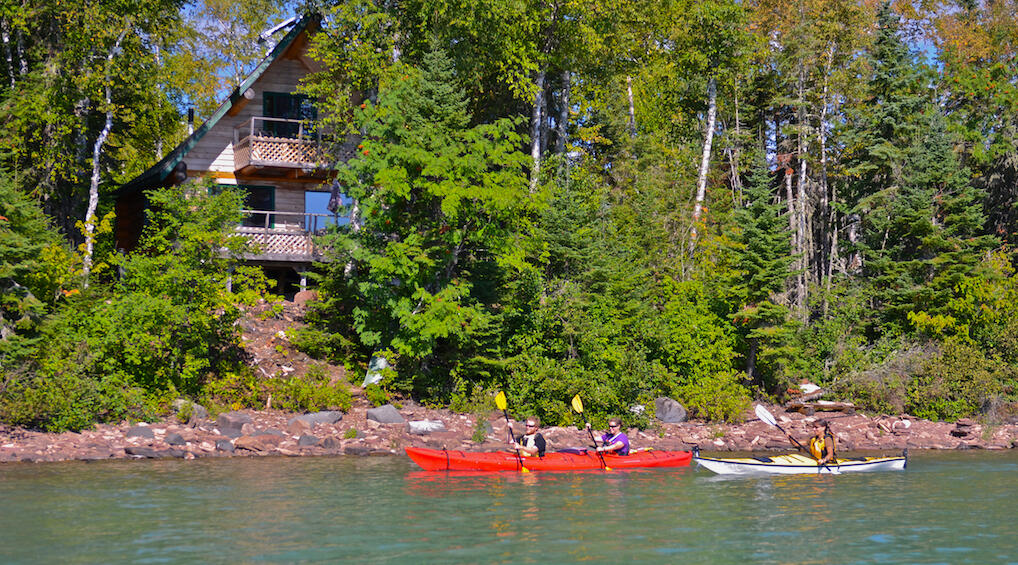 Kayakers paddling by a log cabin.