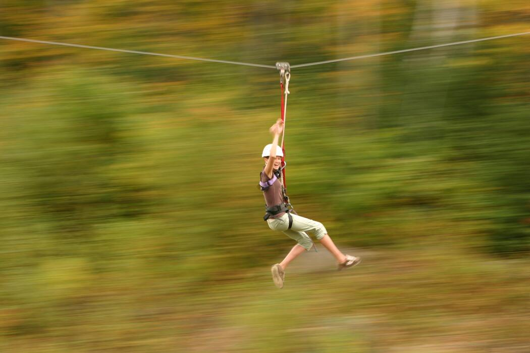 Young woman zipping on a cable.