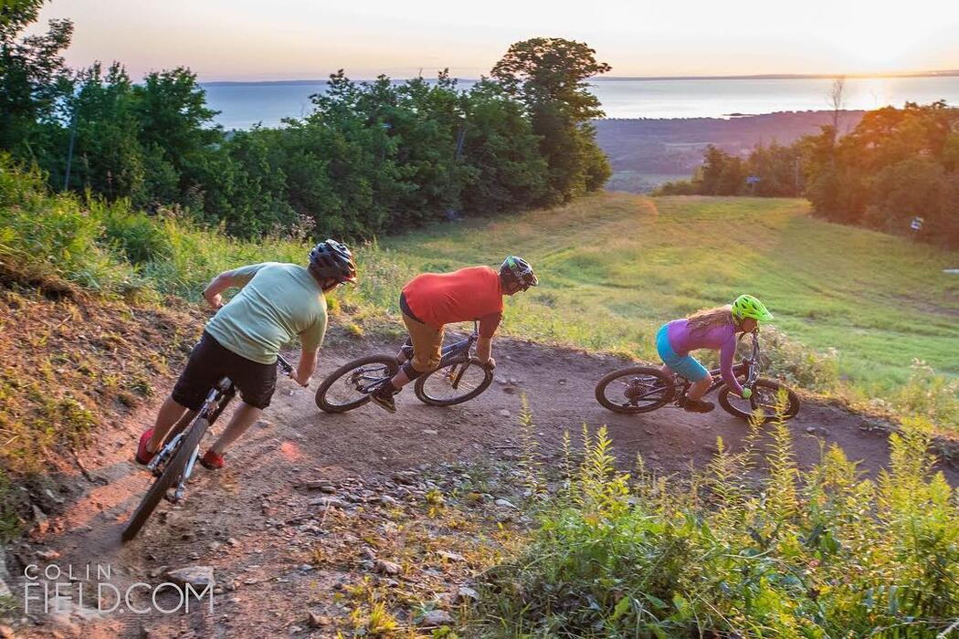 Three people riding mountain bikes on a rocky trail.