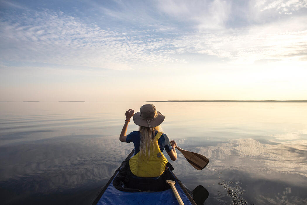 Person in bow of canoe paddling on a calm lake with blue skies above.