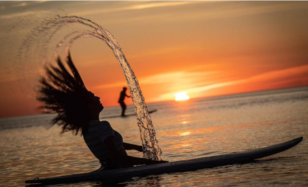 Woman flipping long hair while sitting on a paddleboard at sunset.