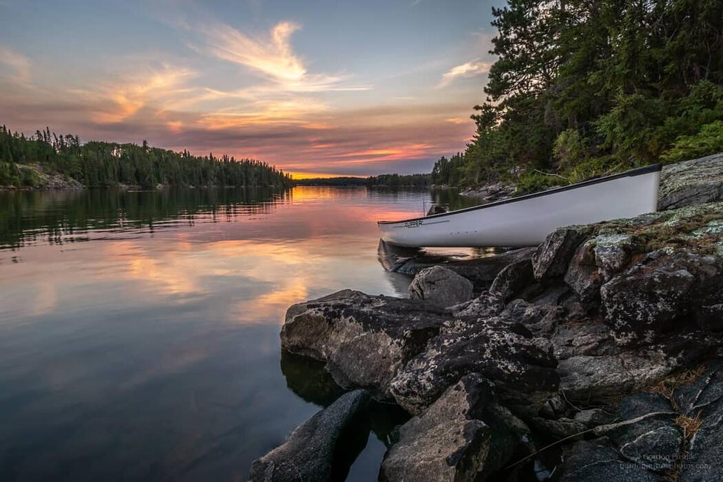Empty white canoe pulled up on shore beside a calm river at sunset.