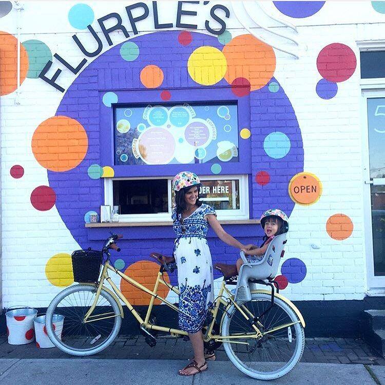 Woman and young child on a two seat bicycle in front of colourful sign.