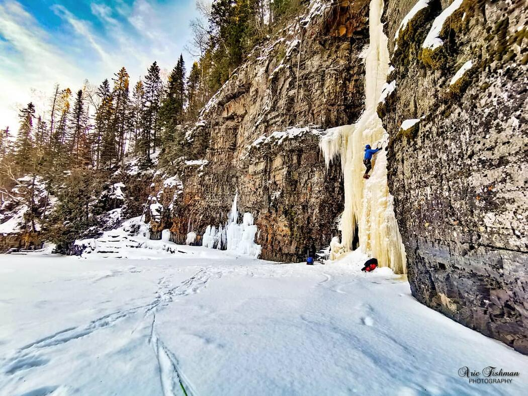 A climber ascending an ice covered rock face  beside a snow covered  lake.